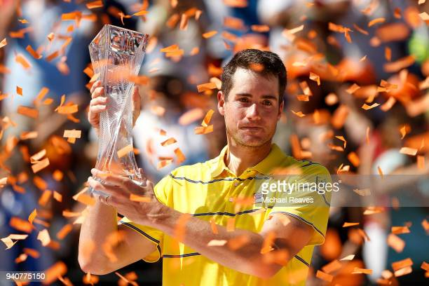 John Isner of the United States poses for a photo with the Butch Buchholz Trophy after defeating Alexander Zverev of Germany in the men's final on...