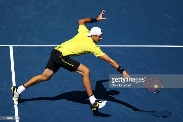 John Isner of the United States returns a shot against Andy Murray of Great Britain during Day Twelve of the 2011 US Open at the USTA Billie Jean...