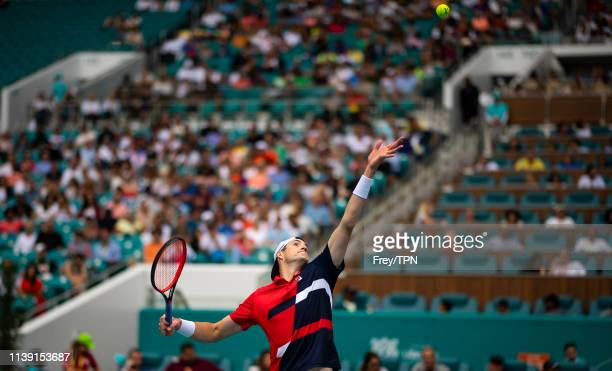 John Isner of The United States serves against Felix Auger-Aliassime of Canada in the semi final of the men's singles at the Miami Open at the Hard...