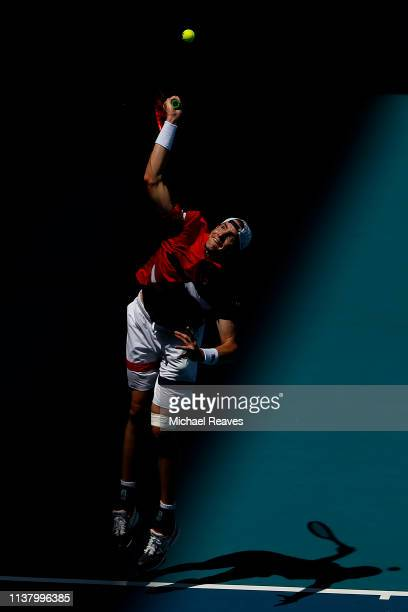 John Isner of the United States serves to Albert Ramos Vinolas of Spain during Day 7 of the Miami Open Presented by Itau at Hard Rock Stadium on...