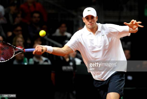 John Isner of the US returns a ball to World number three tennis player Roger Federer of Switzerland during a Davis Cup World Group first round game...