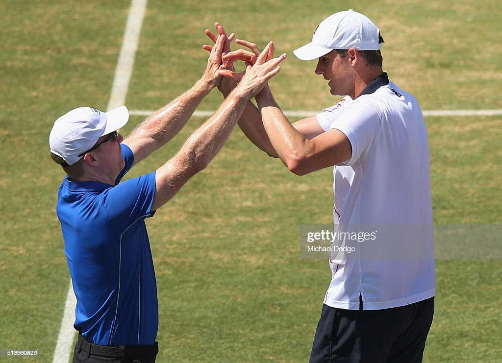 John Isner of the USA celebrates winning match point with Captain Jim Courier in his match against Bernard Tomic of Australia during the Davis Cup tie between Australia and the United States at Kooyong on March 6, 2016 in Melbourne, Australia.