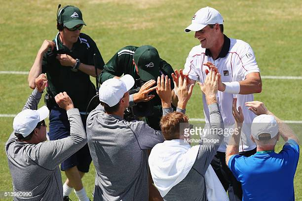 John Isner of the USA celebrates winning match point with his team in his match against Bernard Tomic of Australia during the Davis Cup tie between...