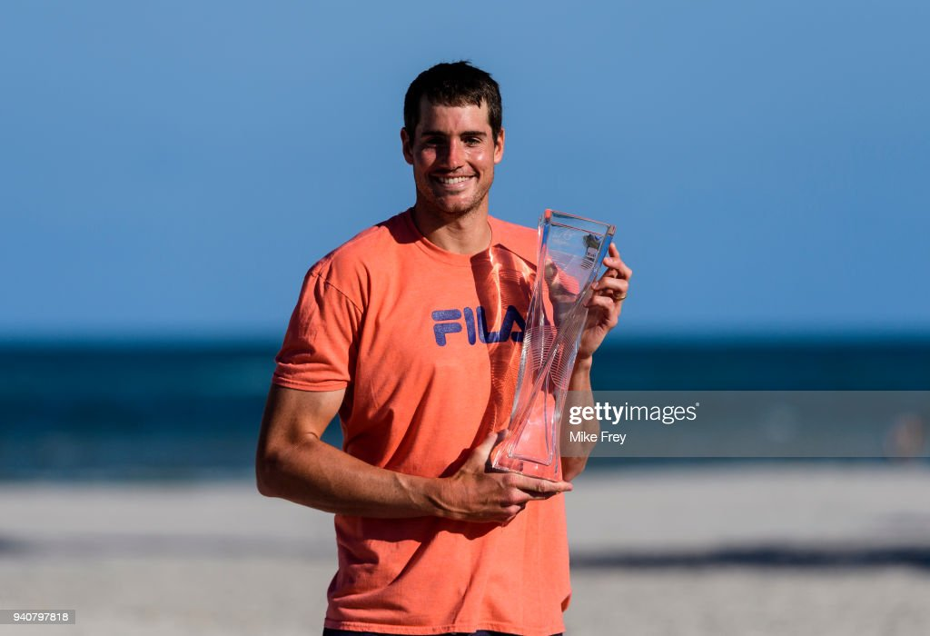 John Isner of the USA poses on Crandon Park Beach with the trophy after beating Alexander Zverev of Germany 6-7 6-4 6-4 in the men's final on Day 14 of the Miami Open Presented by Itau at Crandon Park Tennis Center on April 01, 2018 in Key Biscayne, Florida.