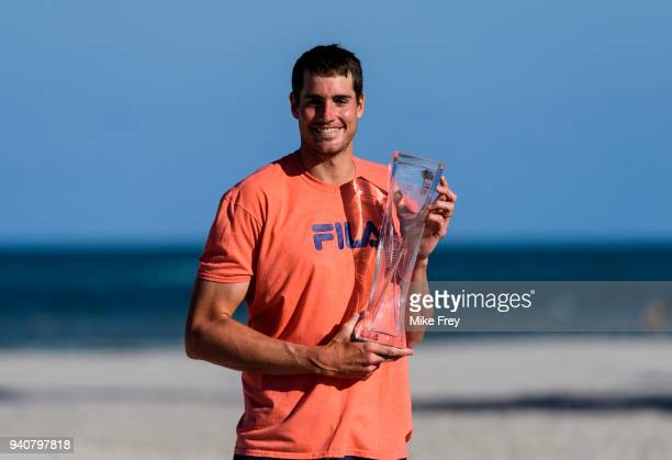 John Isner of the USA poses on Crandon Park Beach with the trophy after beating Alexander Zverev of Germany 67 64 64 in the men's final on Day 14 of...