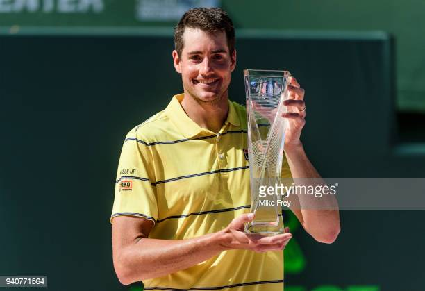 John Isner of the USA poses with the trophy after beating Alexander Zverev of Germany 67 64 64 in the men's final on Day 14 of the Miami Open...