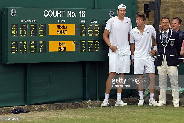 John Isner of USA poses after winning on the third day of his first round match against Nicolas Mahut of France with Chair Umpire Mohamed Lahyani on...