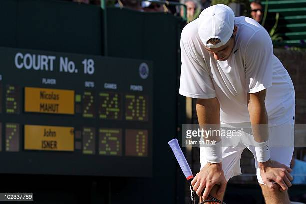 John Isner of USA reacts during his first round match against Nicolas Mahut of France on Day Three of the Wimbledon Lawn Tennis Championships at the...