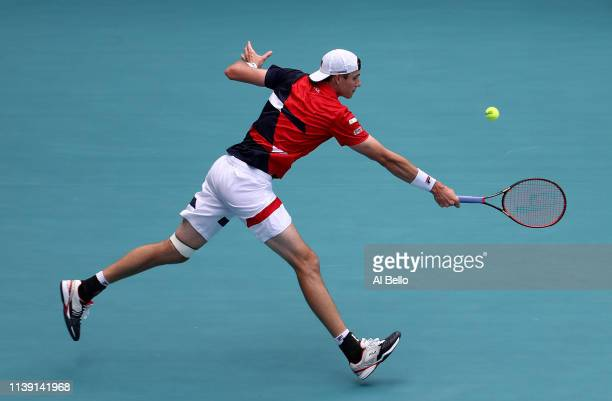 John Isner plays a point against Felix Auger Aliassime of Canada during day 12 of the Miami Open presented by Itau at Hard Rock Stadium on March 29...