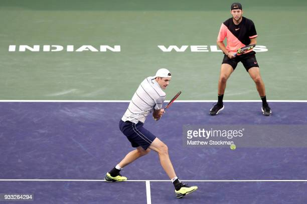 John Isner returns a shot to Mike Bryan and Bob Bryan while playing with Jack Sock during the men's doubles final on Day 13 of the BNP Paribas Open...