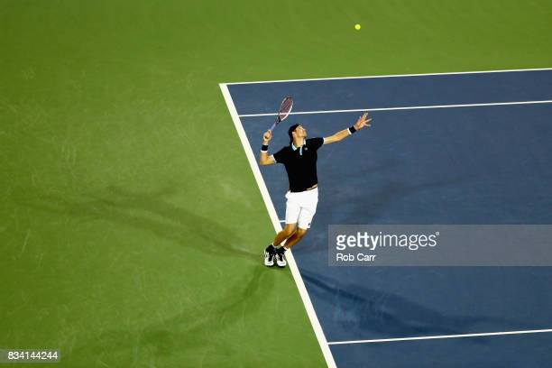 John Isner serves to Frances Tiafoe during Day 6 of the Western and Southern Open at the Linder Family Tennis Center on August 17, 2017 in Mason,...