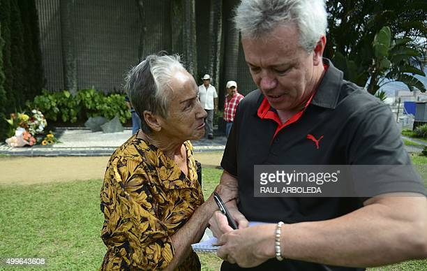 "John Jairo Velasquez, A.K.A ""Popeye"", signs a bank note for a woman beside the tomb of Colombian drug lord Pablo Escobar at the Montesacro cemetery..."