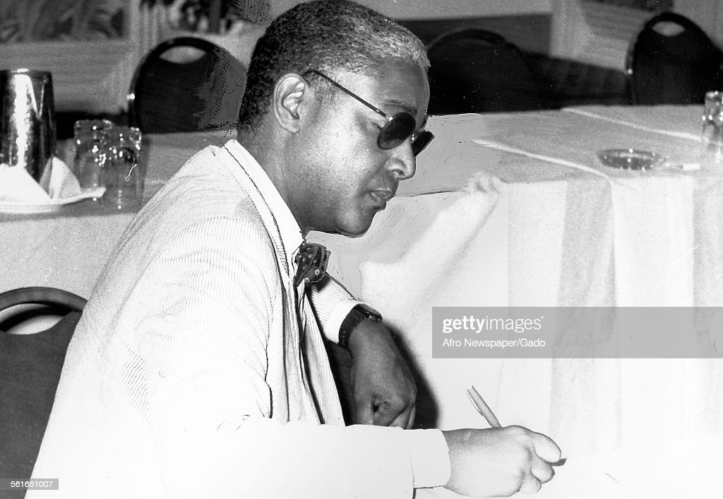 John Jake Oliver, the publisher of Afro American newspaper in Baltimore, seated writing with a pen, Baltimore, Maryland, 1961.