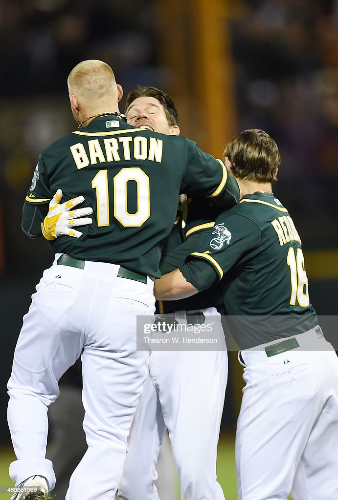 John Jaso #5 of the Oakland Athletics celebrates with Daric Barton #10 and Josh Reddick #16 after Jaso hit a walk-off RBI double scoring Nick Punto #1 (not pictured) to defeat the Washington Nationals in the bottom of the tenth inning 4-3 at O.co Coliseum on May 10, 2014 in Oakland, California.