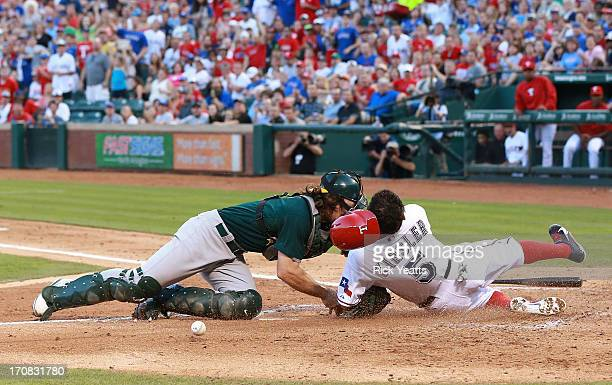 John Jaso of the Oakland Athletics drops the ball after colliding with Ian Kinsler of the Texas Rangers allowing Kinsler to score in the third inning...