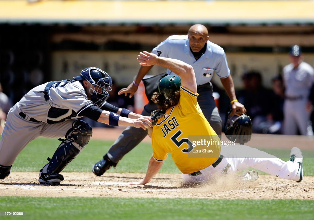 John Jaso #5 of the Oakland Athletics slides safely under the tag of Chris Stewart #19 of the New York Yankees to score on a hit by Seth Smith #15 of the Oakland Athletics in the third inning at O.co Coliseum on June 13, 2013 in Oakland, California.