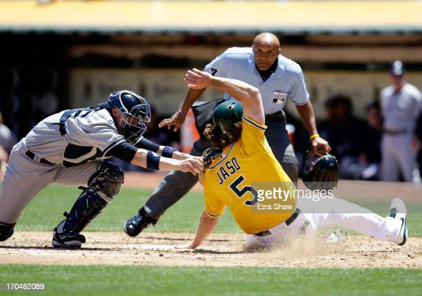 John Jaso of the Oakland Athletics slides safely under the tag of Chris Stewart of the New York Yankees to score on a hit by Seth Smith of the...