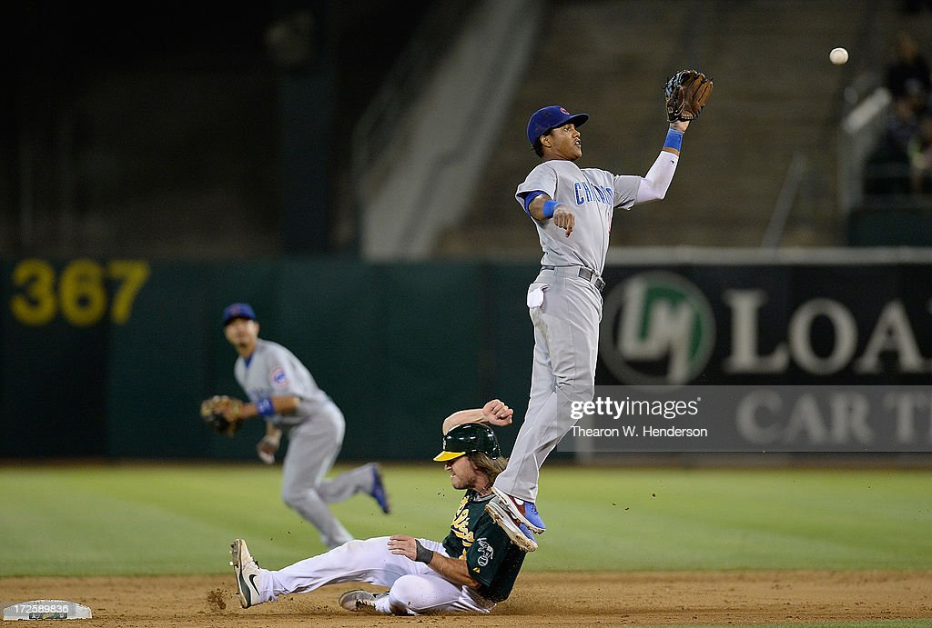 John Jaso #5 of the Oakland Athletics steals second base as Starlin Castro #13 of the Chicago Cubs has to leap to keep the ball from going into centerfield in the ninth inning at O.co Coliseum on July 3, 2013 in Oakland, California.