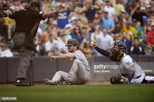 John Jaso of the Pittsburgh Pirates beats a tag at home plate by Manny Pina of the Milwaukee Brewers during the seventh inning of a game at Miller...