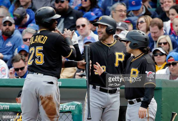 John Jaso of the Pittsburgh Pirates congratulates Gregory Polanco after scoring against the Chicago Cubs on an RBI double by David Freese during the...