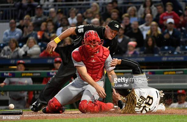 John Jaso of the Pittsburgh Pirates slides safely past Stuart Turner of the Cincinnati Reds to score in the second inning during the game at PNC Park...