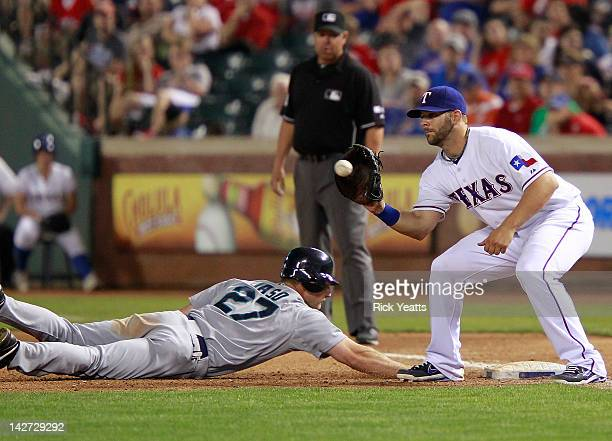 John Jaso of the Seattle Mariners beats the tag by Mitch Moreland of the Texas Rangers at Rangers Ballpark in Arlington on April 11 2012 in Arlington...