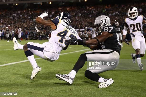 John Johnson of the Los Angeles Rams intercepts a pass intended for Jared Cook of the Oakland Raiders in the endzone during their NFL game at...