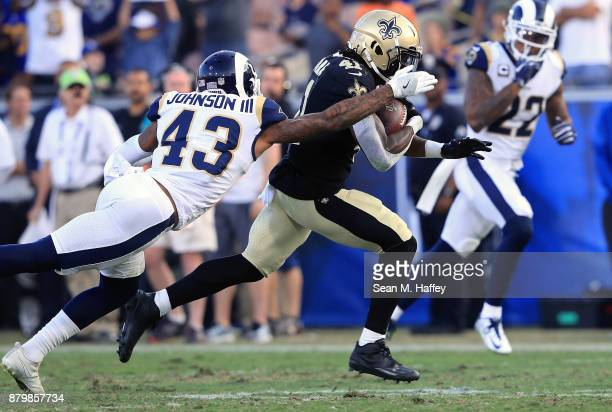 John Johnson of the Los Angeles Rams tackles Alvin Kamara of the New Orleans Saints during the NFL game at the Los Angeles Memorial Coliseum on...