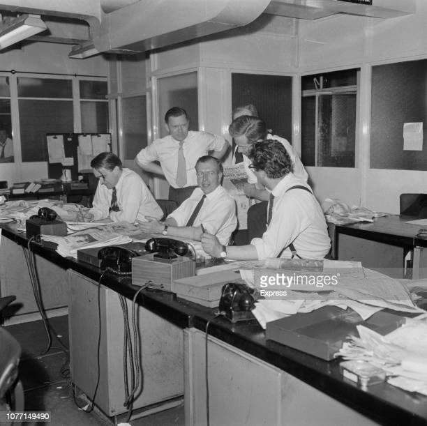 John Junor editor in chief of the Sunday Express newspaper pictured in centre with picture editor Philip Snowdon and other senior staff of the paper...