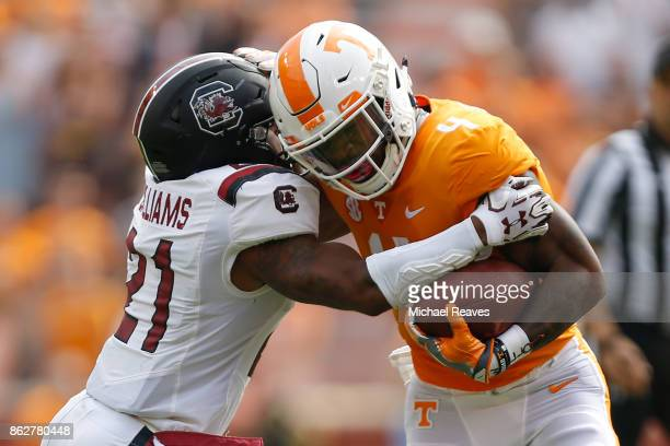 John Kelly of the Tennessee Volunteers breaks a tackle from Jamyest Williams of the South Carolina Gamecocks at Neyland Stadium on October 14 2017 in...