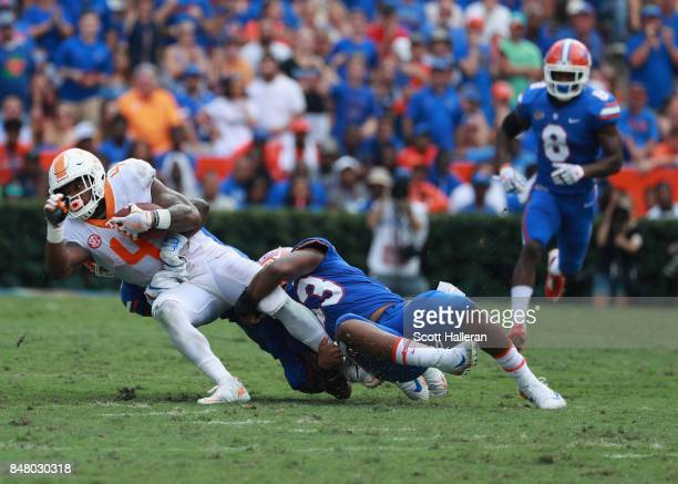 John Kelly of the Tennessee Volunteers is tackled by David Reese of the Florida Gators in the first half of their game at Ben Hill Griffin Stadium on...