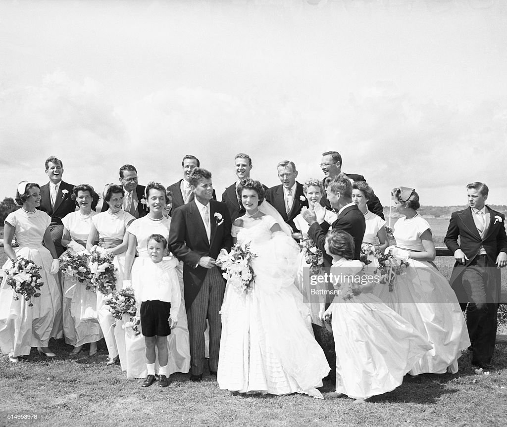 John Kennedy, Jacqueline Kennedy, and their wedding party at Hammersmith Farm in Newport after the wedding. Robert Kennedy in standing in profile beside Jackie; Ted Kennedy is laughing at the far left.