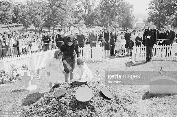 John Kennedy Jr places a 'PT109' tie clasp on the grave of his father as his mother and sister watch They are visiting the cemetery on what would...