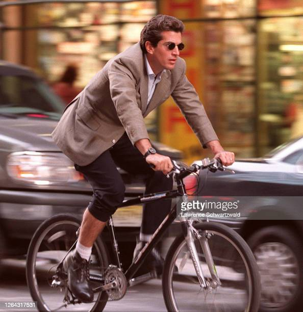 John Kennedy, Jr. Shows a little leg while he bicycles on 7th ave and 56th st. Late today thru rush hour traffic.