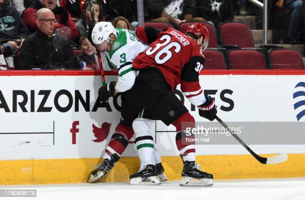 John Klingberg of the Dallas Stars and Christian Fischer of the Arizona Coyotes battle for the puck along the boards during the first period of the...