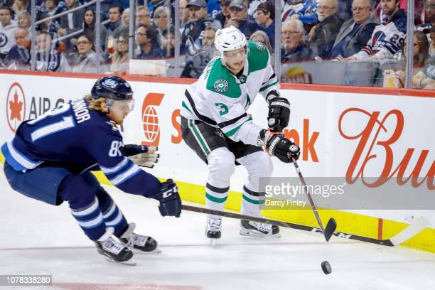 John Klingberg of the Dallas Stars and Kyle Connor of the Winnipeg Jets battle for the puck during first period action at the Bell MTS Place on...