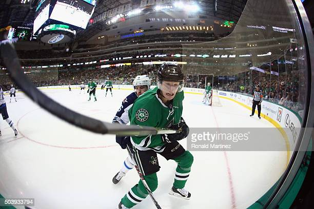 John Klingberg of the Dallas Stars is checked by Alexander Burmistrov of the Winnipeg Jets in the second period at American Airlines Center on...