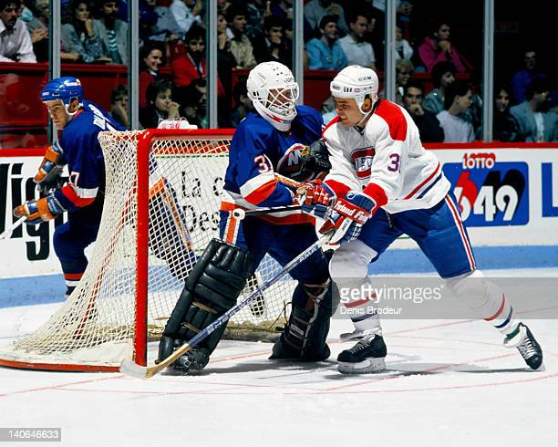 John Kordic of the Montreal Canadiens skates through the crease of the New York Islanders net and bumps with Goaltender Billy Smith Circa 1980 at the...