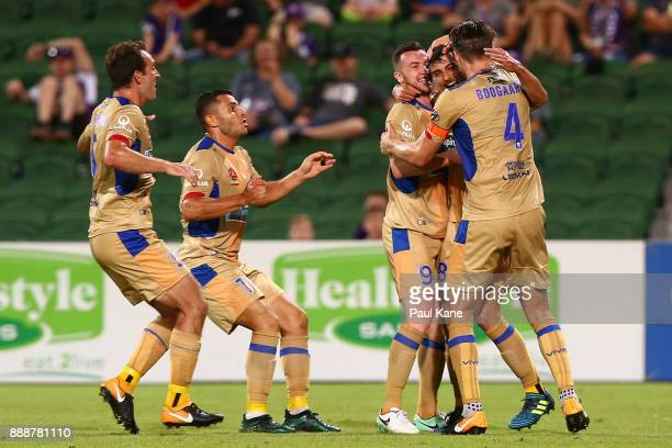 John Koutroumbis of the Jets is congratulated by team mates after scoring the equaliser during the round 10 ALeague match between the Perth Glory and...