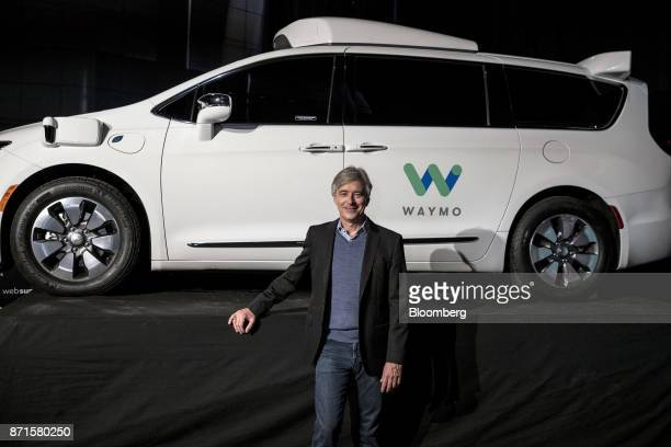 John Krafcik chief executive officer of Waymo LLC poses for a photograph in front of a Waymo selfdriving automobile at the Lisbon Web Summit in...