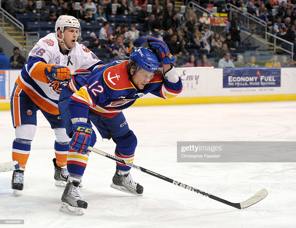 John Kurtz #12 of the Norfolk Admirals grabs his helmet as he is cross checked by Matt Donovan #46 of the Bridgeport Sound Tigers during an American Hockey League game on February 2, 2013 at the Webster Bank Arena at Harbor Yard in Bridgeport, Connecticut.