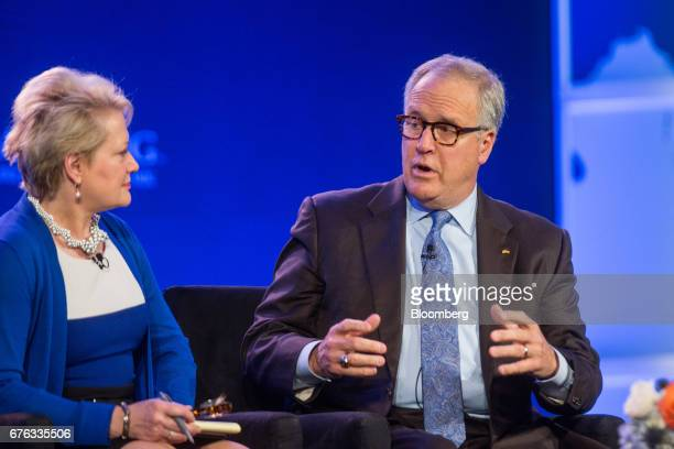John Lechleiter former president and chief executive officer of Eli Lilly Co right speaks as Susan Dentzer chief executive officer of Network for...