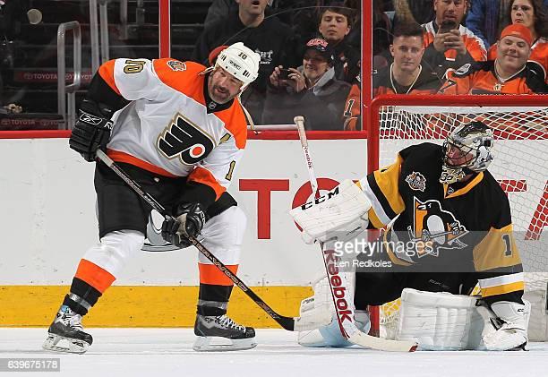 John LeClair of the Philadelphia Flyers Alumni positions himself on a scoring opportunity against Jocelyn Thibault of the Pittsburgh Penguins Alumni...