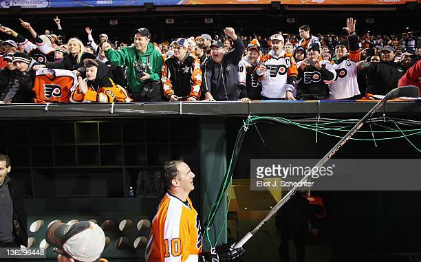 John LeClair of the Philadelphia Flyers hands his stick to a fan after the Alumni Game against the New York Rangers during the on December 31 2011 in...