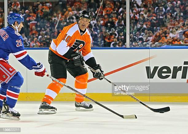 John LeClair of the Philadelphia Flyers skates the puck against the New York Rangers during the Alumni Game prior to the 2012 NHL Bridgestone Winter...