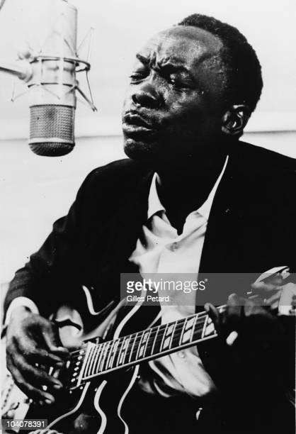 John Lee Hooker sings at a microphone in a recording studio in 1967 in the United States