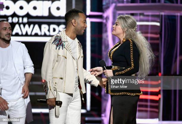 John Legend and Kelly Clarkson speak onstage during the 2018 Billboard Music Awards at MGM Grand Garden Arena on May 20 2018 in Las Vegas Nevada