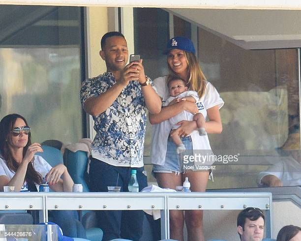John Legend Luna Simone Stephens and Chrissy Teigen attend a baseball game between the Colorado Rockies and the Los Angeles Dodgers at Dodger Stadium...