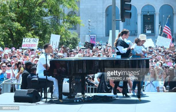 John Legend sings at the piano as Chrissy Teigen holding their baby walks off stage during a 'Familes Belong Together' march and rally in Los Angeles...
