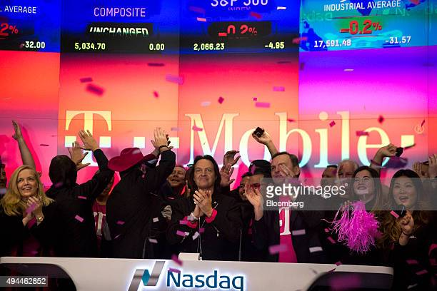 John Legere chief executive officer of TMobile US Inc center applauds after ringing the opening bell at the Nasdaq MarketSite in New York US on...